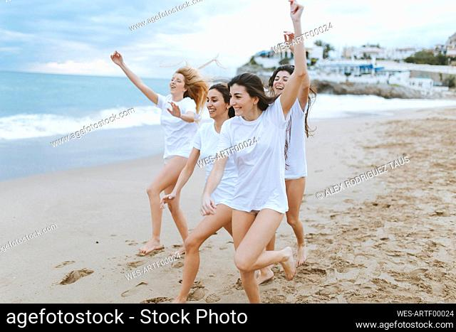 Female friends with arms raised enjoying at beach