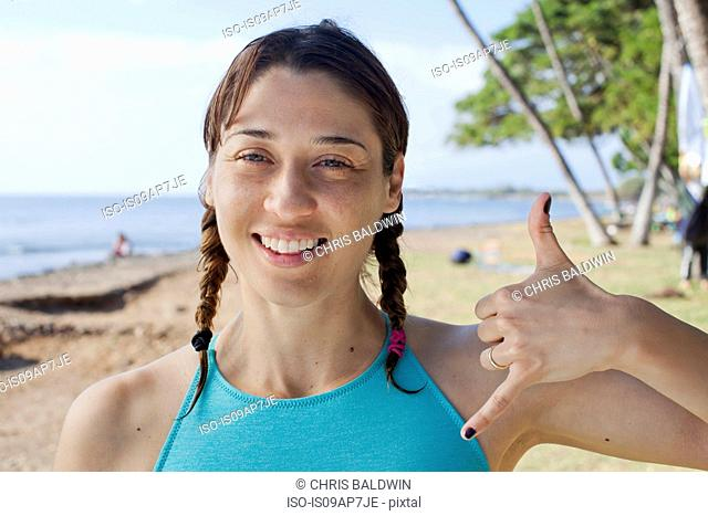 Woman making hand gesture on beach