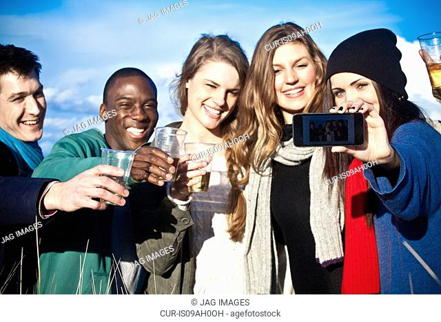 Young adult friends toasting with white wine and taking selfie