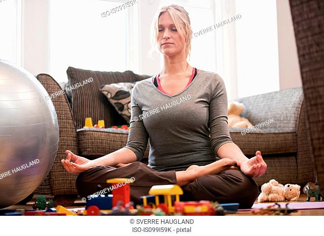 Mid adult woman in yoga pose at home