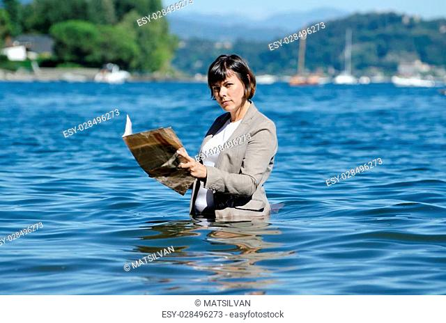 Business woman reading financial newspaper and standing in the lake with her clothes
