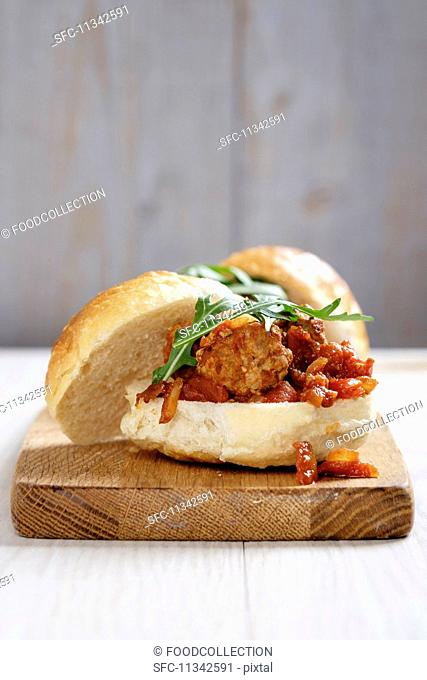 A turkey meatball sandwich with a tomato and onion sauce