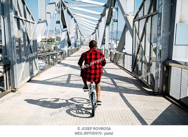 Man riding bicycle on a bridge