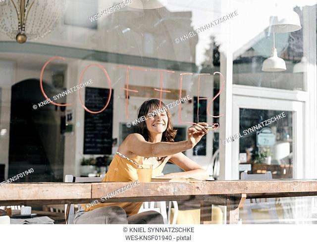 Woman sitting in cafe, writing the word 'coffee' on window pane