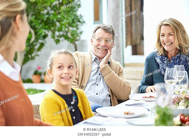 Multi-generation family enjoying lunch at patio table
