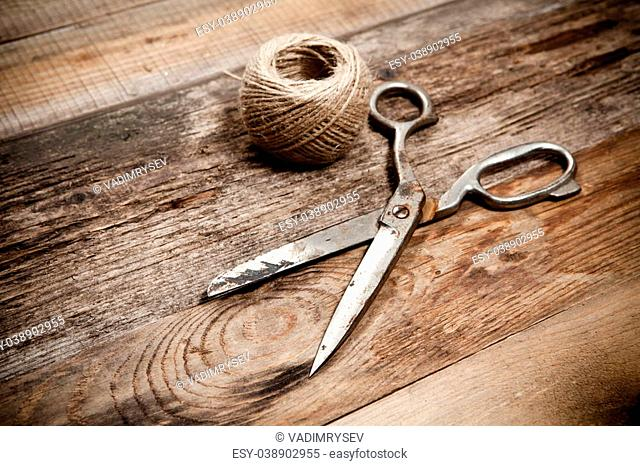 Old rusty scissors and skein jute on wooden table