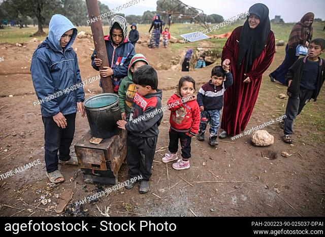 23 February 2020, Syria, Idlib: Syrian children and a woman are pictured outside a cave at Taltouna village. At least eight families live in an ancient deserted...