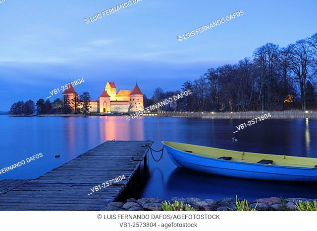 Island castle on Galve lake illuminated at dusk in Autumn with boat and pier in foreground. Trakai, Lithuania