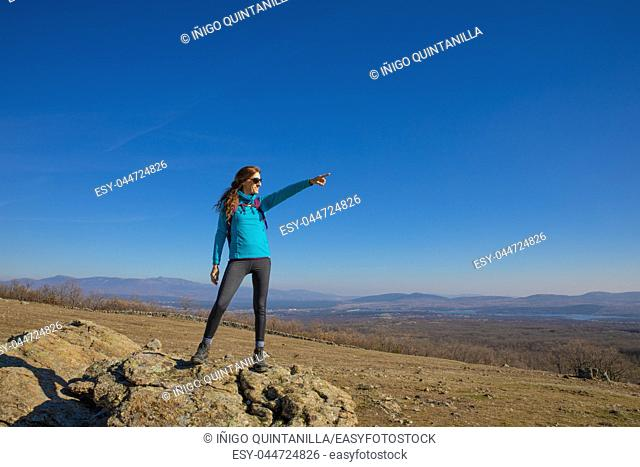 hiker or trekking woman standing on rock, pointing with hand to a text or copy space in blue sky, in Guadarrama Natural Park (Madrid, Spain)