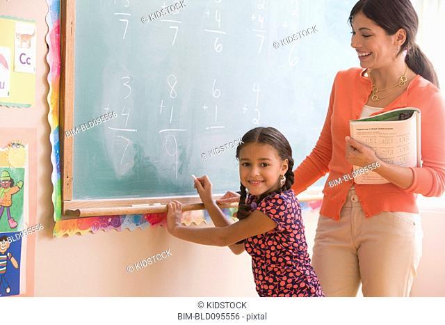 Teacher helping student at blackboard in classroom