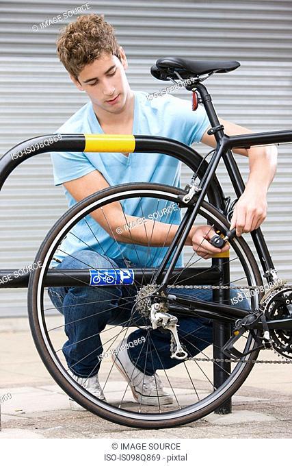 Man locking bicycle