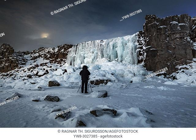 Photographer taking pictures by the frozen Oxararfoss Waterfall, Thingvellir National Park, Iceland. Unesco World Heritage Site