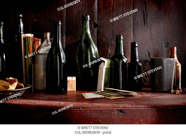Empty vintage beer bottles and playing cards on pub shelf