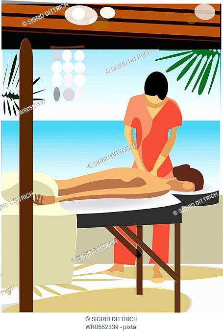 young woman getting massage by female therapist - next to the sea