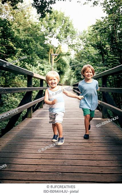 Full length front view of boys running over wooden bridge looking at camera smiling, Bludenz, Vorarlberg, Austria