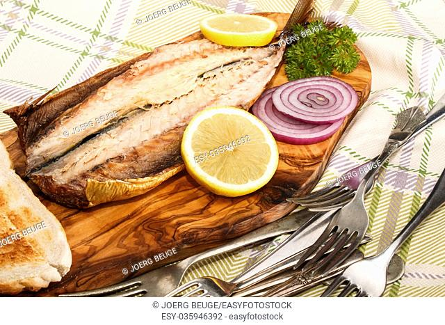 smoked mackerel on a wooden board with lemon slices, purple onion and toast bread
