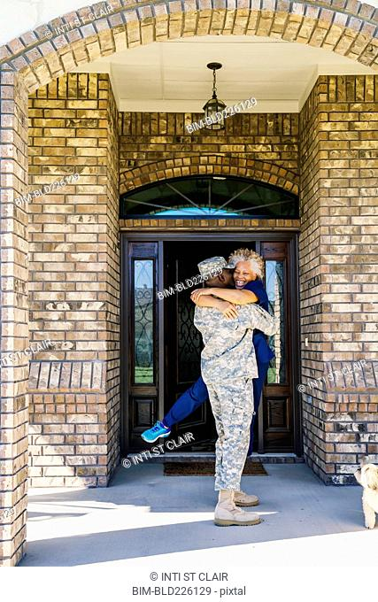 Black soldier hugging wife in doorway