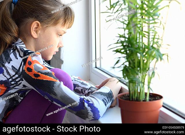 Upset girl sitting by the window and looking very sad out the window