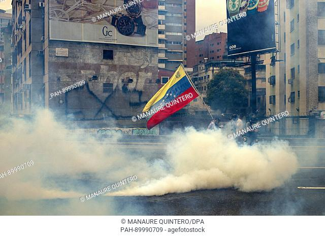 Protesters wearing masks amid a tear-gas cloud in Caracas, Venezuela, 19 April 2017, where mass demonstrations turned into riots