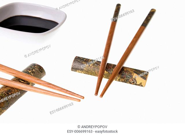 Two pairs of wooden chopsticks and soy sauce. Sticks are decorated with temple theme ornamentation. Isolated on white
