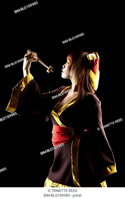 Asian woman in traditional clothing holding sushi on chopsticks