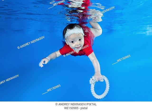 Litle girl in red dress posing under water in swimming pool, Odessa, Ukraine