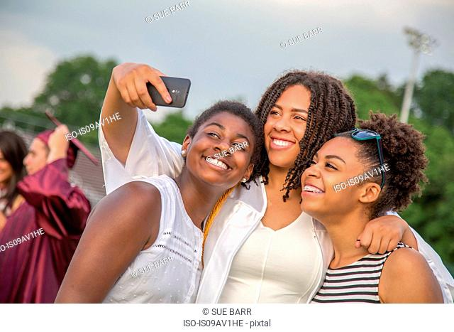 Teenage girl and sisters posing for smartphone selfie at graduation ceremony