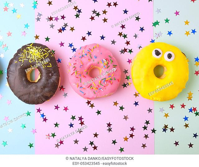 round donuts with various fillings and sprinkles on an abstract color background with festive decor