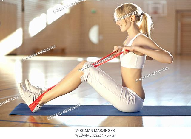 Germany, Mauern, Woman sitting and stretching rubber band, smiling, looking away