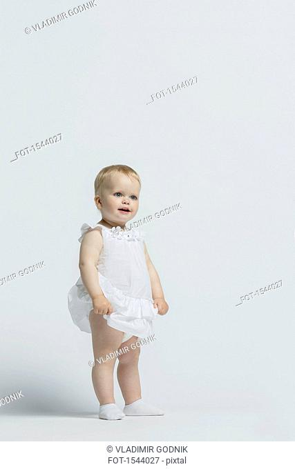 Girl wearing dress standing against white background