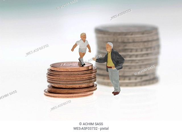Plastic figurines and stack of coins