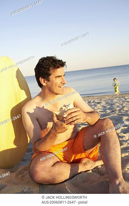 Close-up of a mature man sitting on the beach and holding a seashell