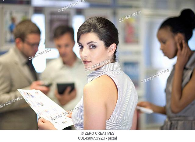 Young businesswoman looking over her shoulder in meeting