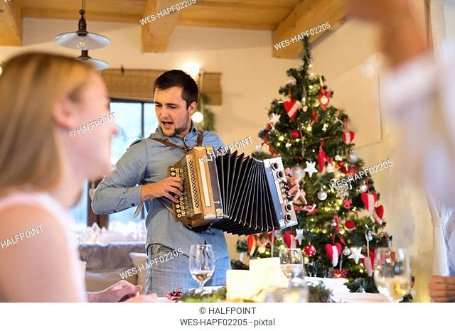 Young man playing accordion at Christmas dinner table