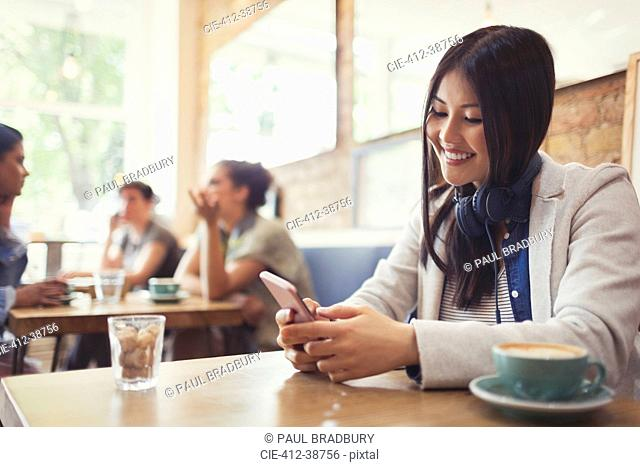 Smiling young woman with headphones texting with cell phone and drinking coffee at cafe table