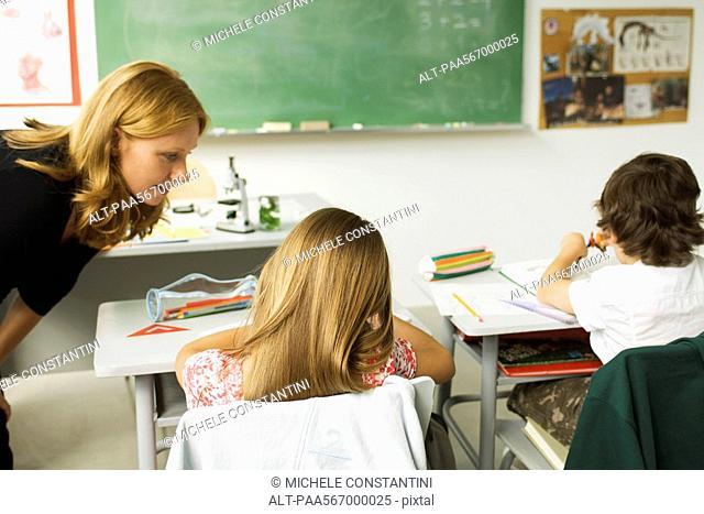 Teacher helping student in elementary classroom