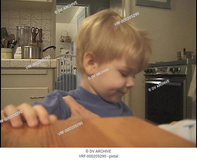 A parent combs a little boy's hair