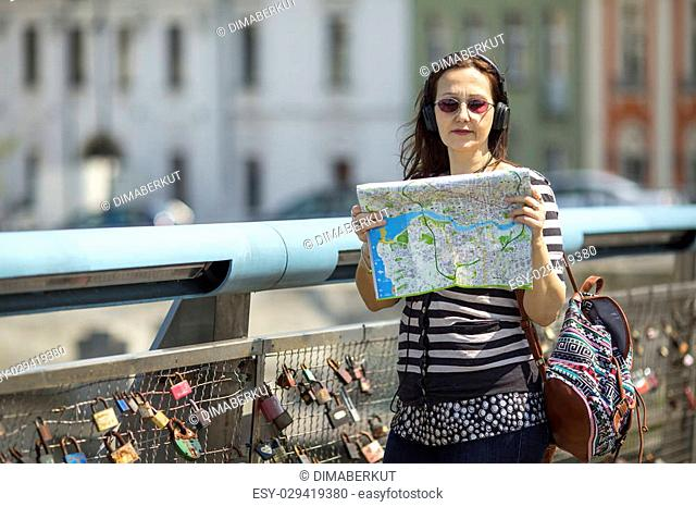 Young female tourist, standing on the pedestrian bridge with locks of love, with map looking for the direction