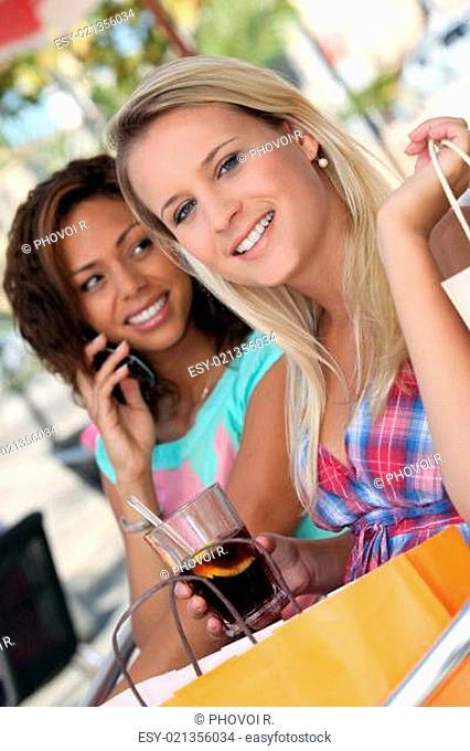 Two women having a soft drink on a terrace