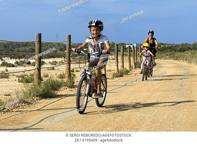 Mother and daughters are riding in a bike. Pudent Lake. Formentera. Balearic Islands, Spain, Europe. Bicycle route