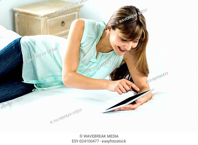 Beautiful woman using digital tablet while relaxing on bed
