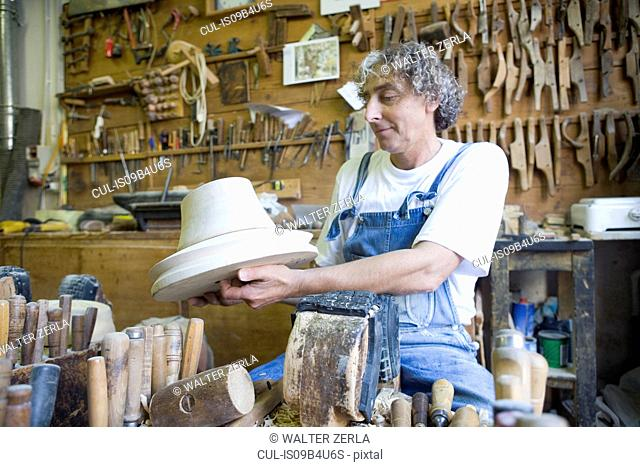 Carpenter admiring wooden mould for headwear in workshop