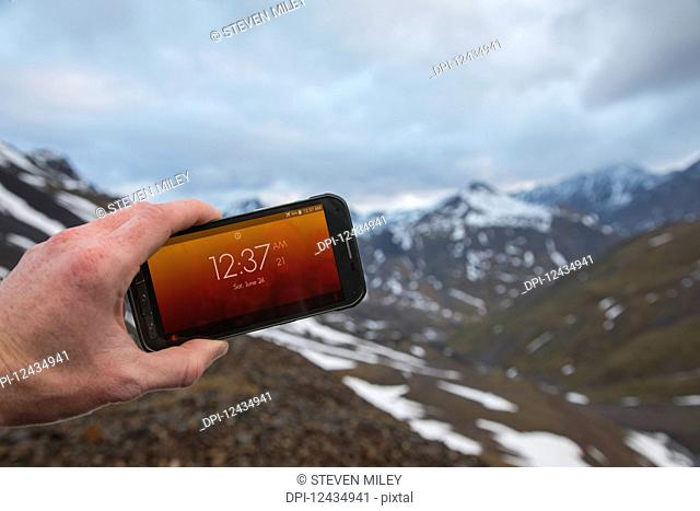 A man displays the time on his phone after midnight on June 24 in the Brooks Range when the sun never sets; Alaska, United States of America