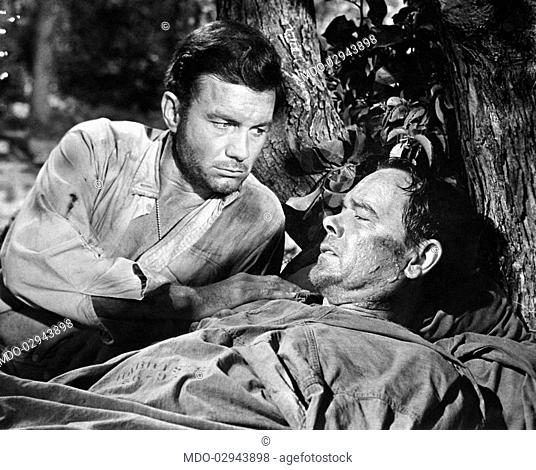 American actor Cliff Robertson comforting American actor Robert Culp wounded in Munson Island, Florida. They're acting in the film Pt 109. USA, 1963