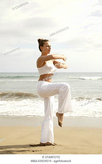 Woman, Tai Chi practice, clothing white, outside, sandy beach, full-length