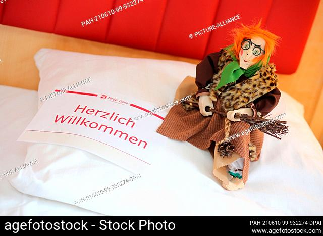 """27 May 2021, Saxony-Anhalt, Wernigerode: A Brocken Witch with the words """"""""Welcome"""""""" sits on the pillow of a room at the Hotel Weißer Hirsch"""