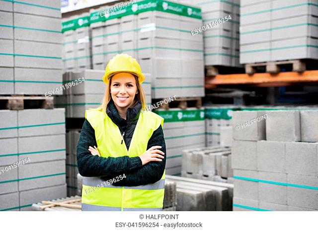 Female worker standing outside a warehouse, arms crossed. Woman in an industrial area