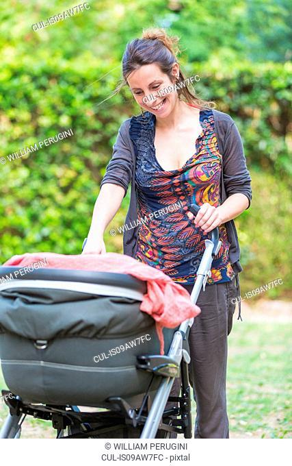 Mother looking at baby girl in pram smiling