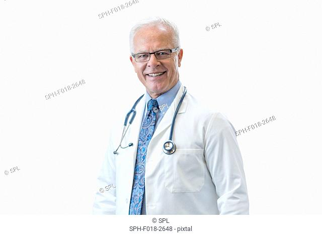 Senior male doctor smiling, studio shot