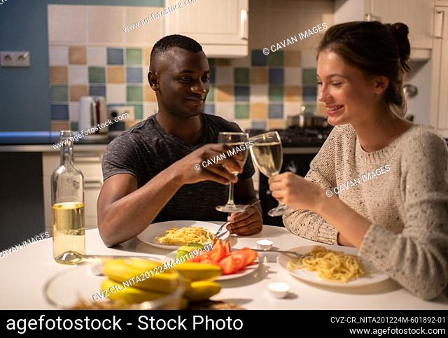 Cheerful diverse couple proposing toast during date